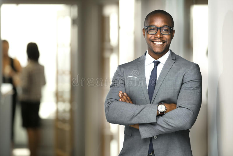 Uomo esecutivo afroamericano allegro bello di affari all'ufficio dell'area di lavoro fotografia stock libera da diritti
