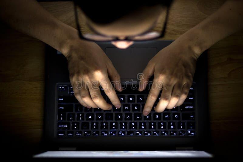 Uomo facendo uso del computer portatile nello scuro immagine stock