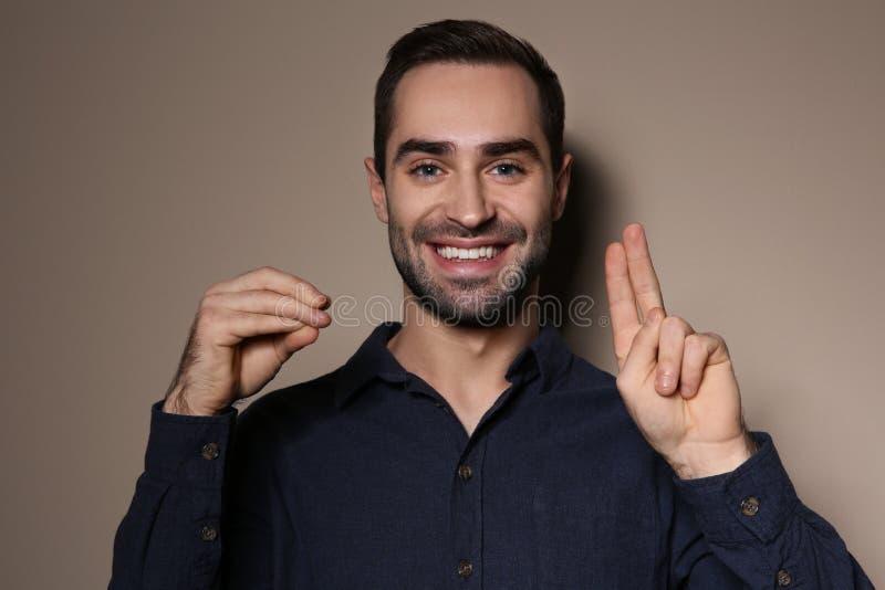 Uomo facendo uso del linguaggio dei segni su fondo immagini stock