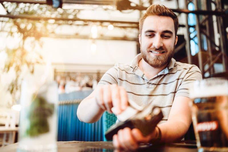 Uomo facendo uso della carta di credito per il pagamento al ristorante fotografia stock