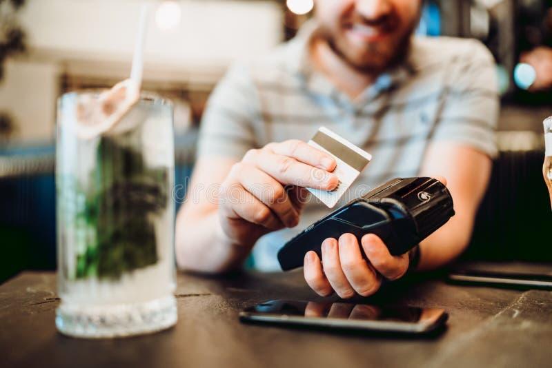 Uomo facendo uso della carta di credito per il pagamento al ristorante immagini stock