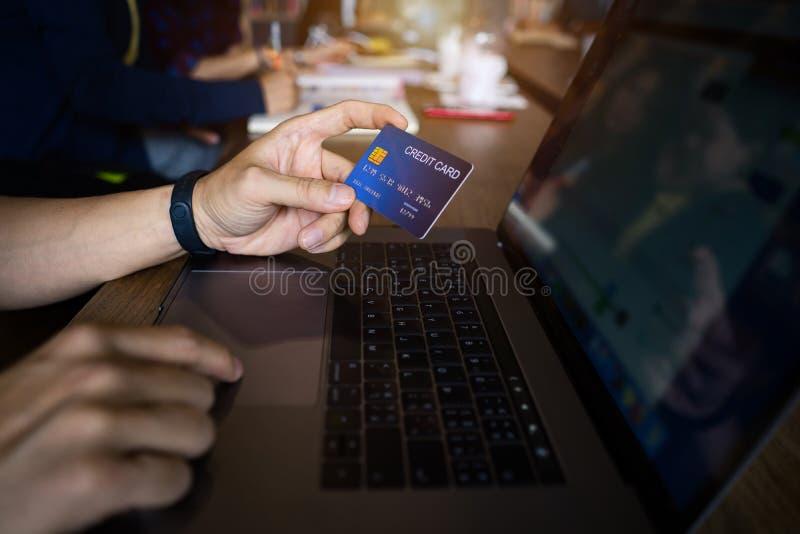 Uomo facendo uso di pagamento con carta di credito che compera online nel caffè pubblico Rischio di frode di dati di Internet immagine stock