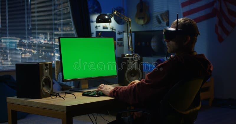 Uomo facendo uso di un computer mentre indossando la cuffia avricolare di VR fotografia stock
