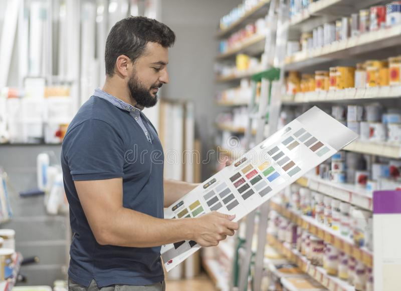 Uomo in farmacia che seleziona colore della pittura per il suo lavoro fotografie stock libere da diritti