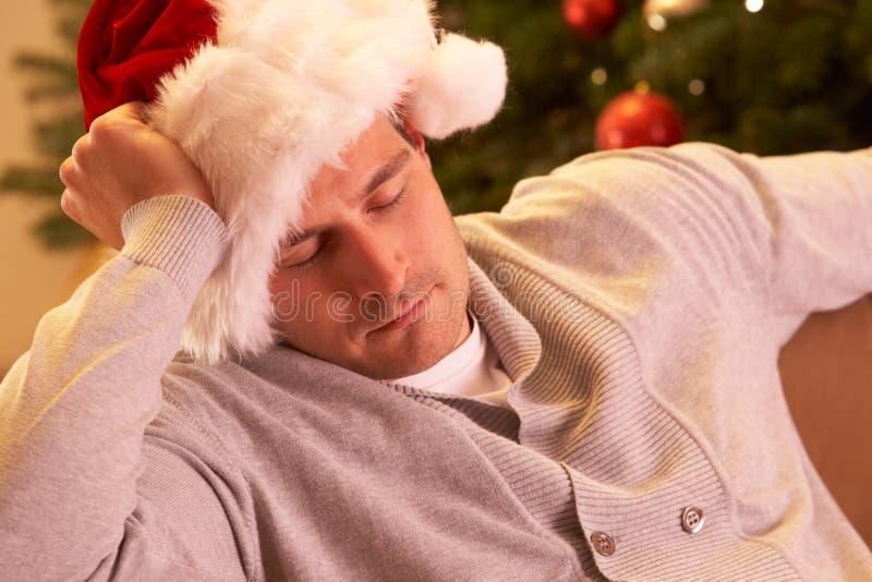 Uomo faticoso che si distende davanti all'albero di Natale immagine stock libera da diritti