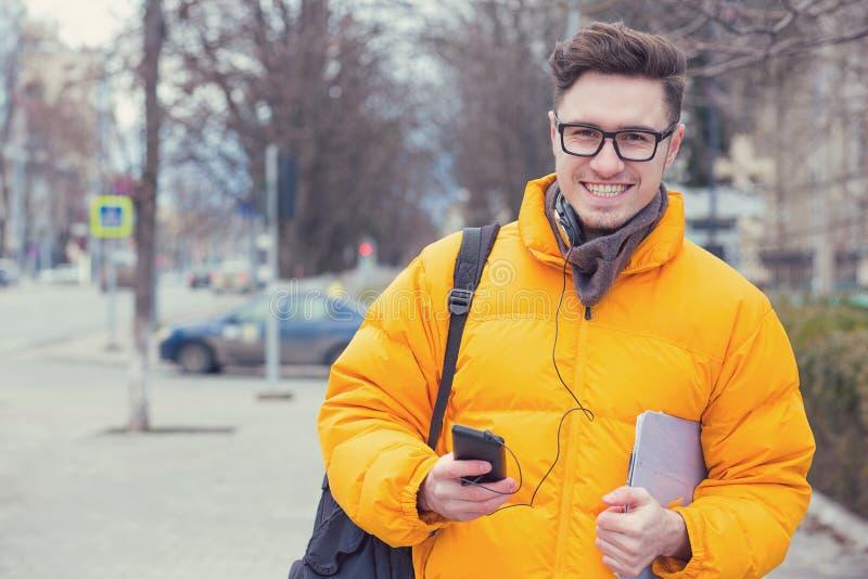 Uomo felice alla moda in cappotto che cammina sulla via immagini stock