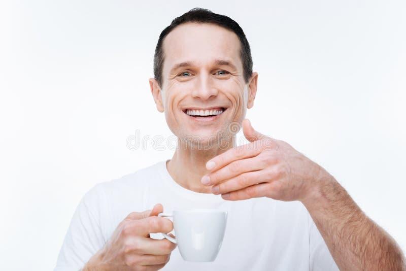 Uomo felice allegro che gode dell'odore del caffè immagine stock libera da diritti