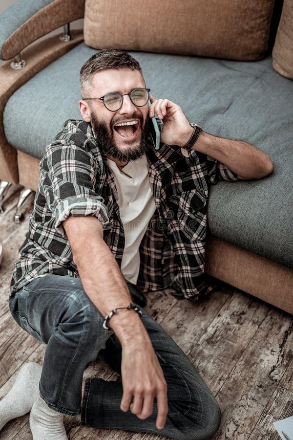 Uomo felice allegro che gode della sua conversazione telefonica immagini stock libere da diritti