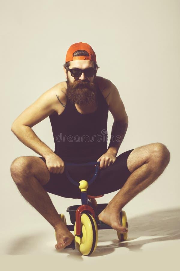 Uomo felice barbuto sul giocattolo variopinto in occhiali da sole, cappuccio della bicicletta fotografia stock