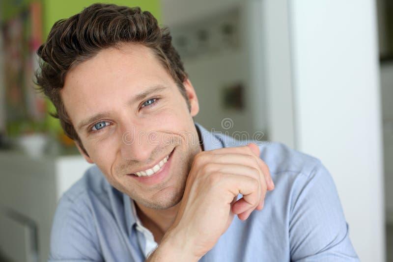 Uomo felice a casa che sorride alla macchina fotografica fotografie stock