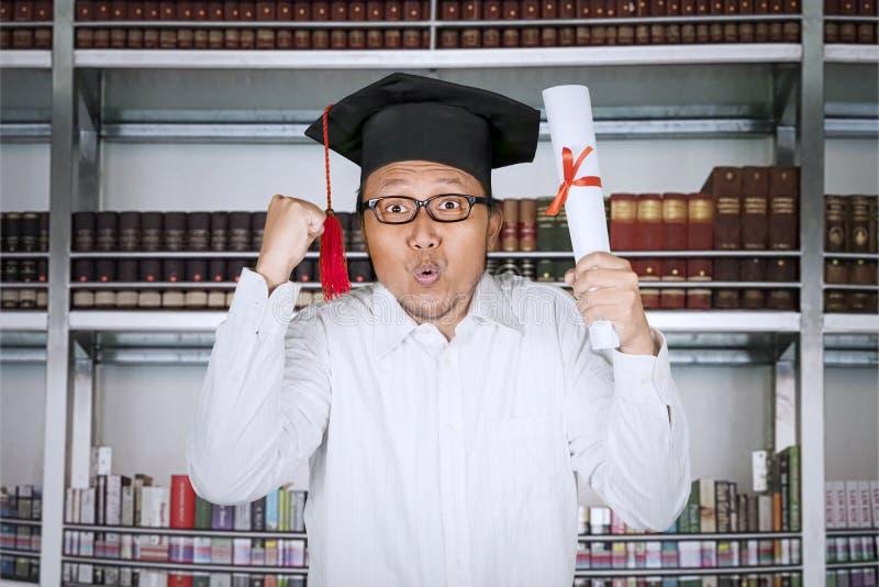 Uomo felice che alza le mani e diploma fotografia stock