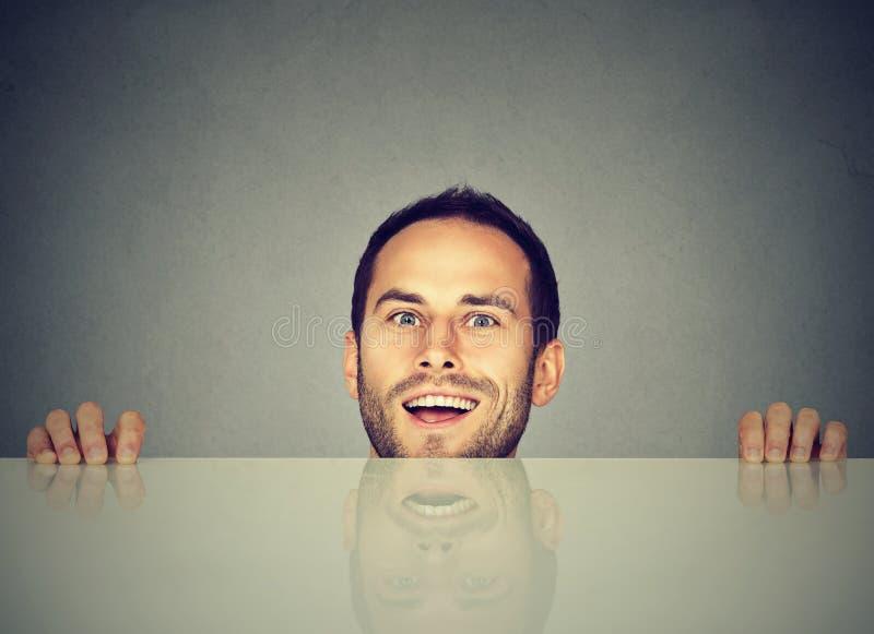 Uomo felice che dà una occhiata da dietro la tavola fotografia stock libera da diritti