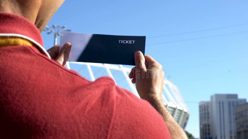 Uomo felice che esamina il biglietto di calcio, vincitore di lotteria fortunato, eccitato prima della partita fotografia stock libera da diritti