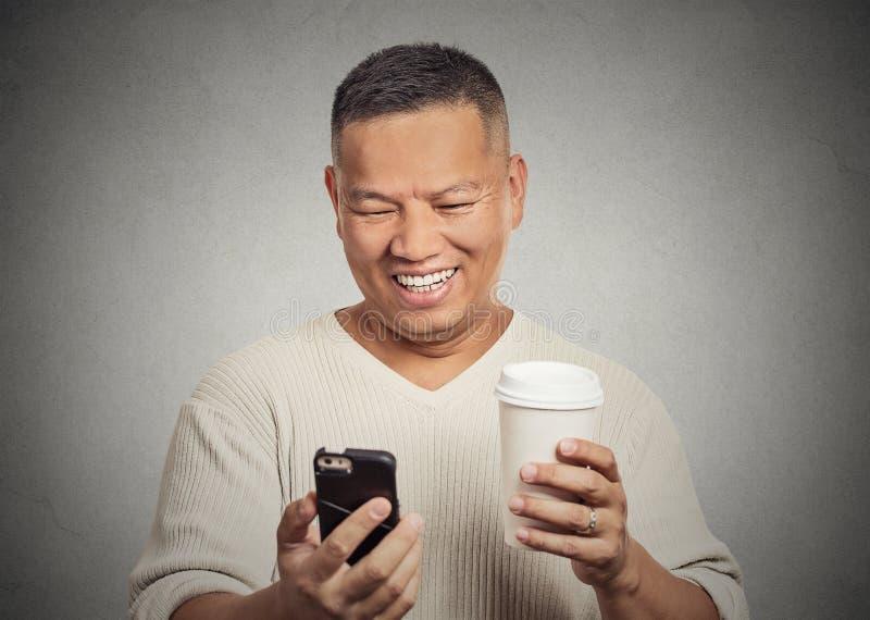Uomo felice che esamina telefono cellulare mobile che tiene il caffè della tazza fotografie stock libere da diritti