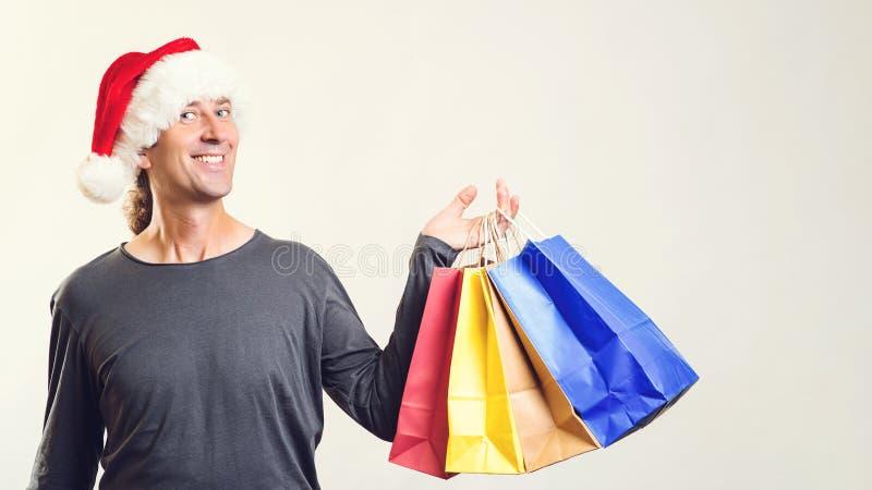 Uomo felice che fa shopping bag L'uomo indossa il cappello di Babbo Natale Natale, vendita, shopping È ora di comprare il natale immagini stock libere da diritti