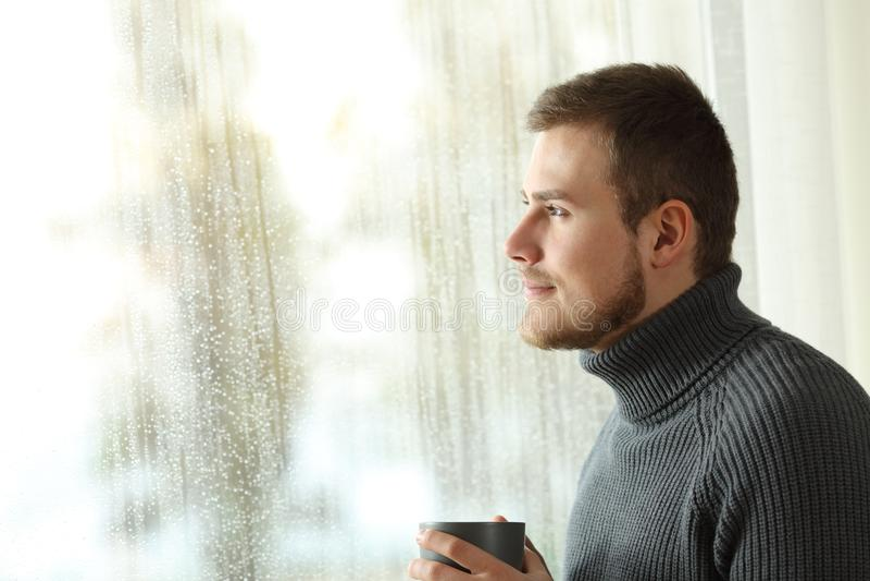 Uomo felice che guarda attraverso una finestra in un giorno piovoso fotografia stock