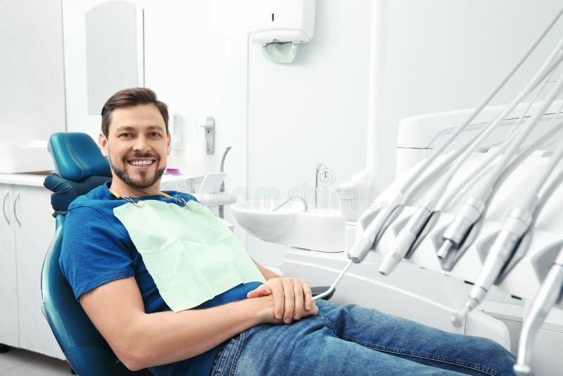 Uomo felice che ha appuntamento del dentista in ufficio immagini stock