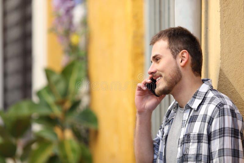 Uomo felice che ha telefonata che sta nella via fotografia stock