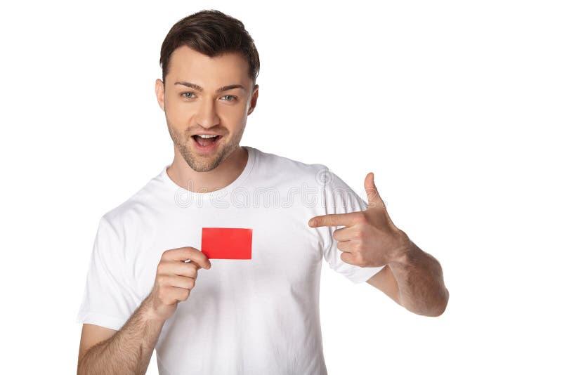 Uomo felice che mostra dal dito sulla carta in bianco fotografia stock