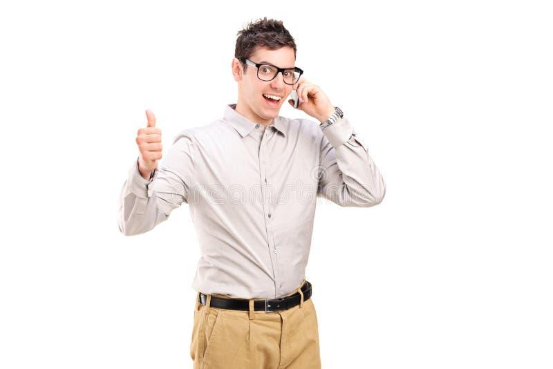 Uomo felice che parla sul telefono e che dà pollice su fotografia stock libera da diritti
