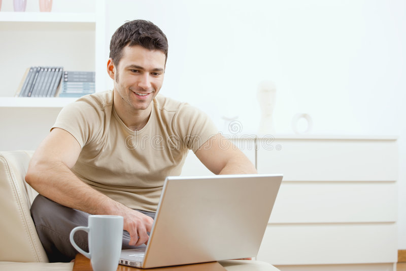 Uomo felice che per mezzo del calcolatore fotografie stock libere da diritti