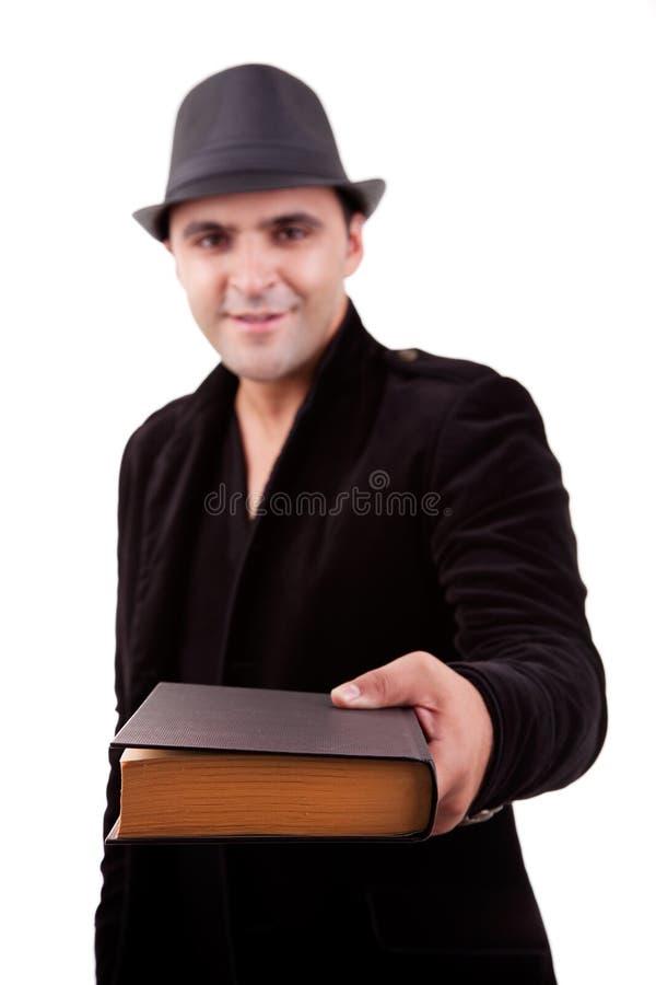 Uomo felice che si leva in piedi offrente un libro immagini stock libere da diritti