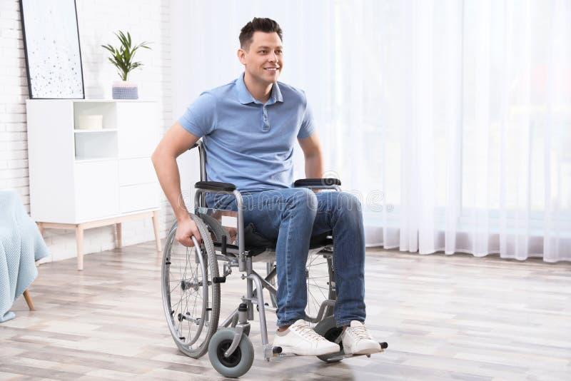 Uomo felice che si siede in sedia a rotelle immagine stock libera da diritti