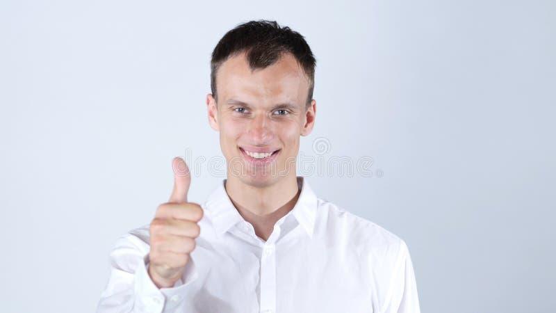 Uomo felice che sorride e che mostra pollice su immagini stock