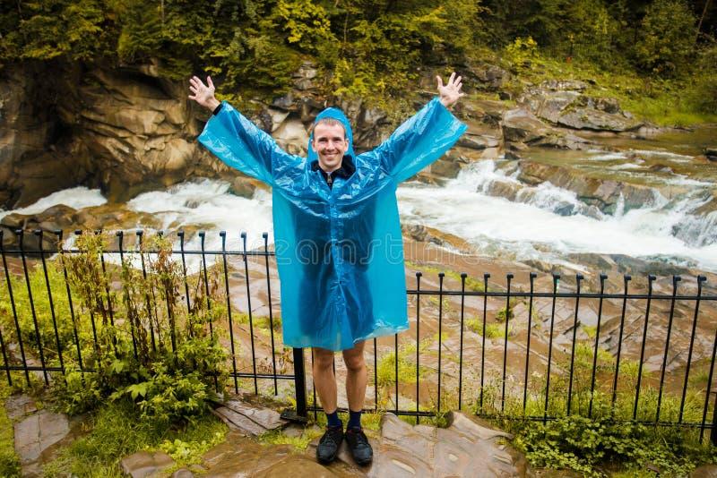 Uomo felice che sta con le armi stese in pioggia immagini stock libere da diritti