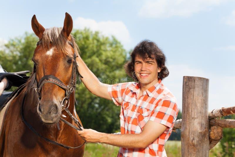 Uomo felice che tiene il suo bello cavallo da una briglia fotografia stock