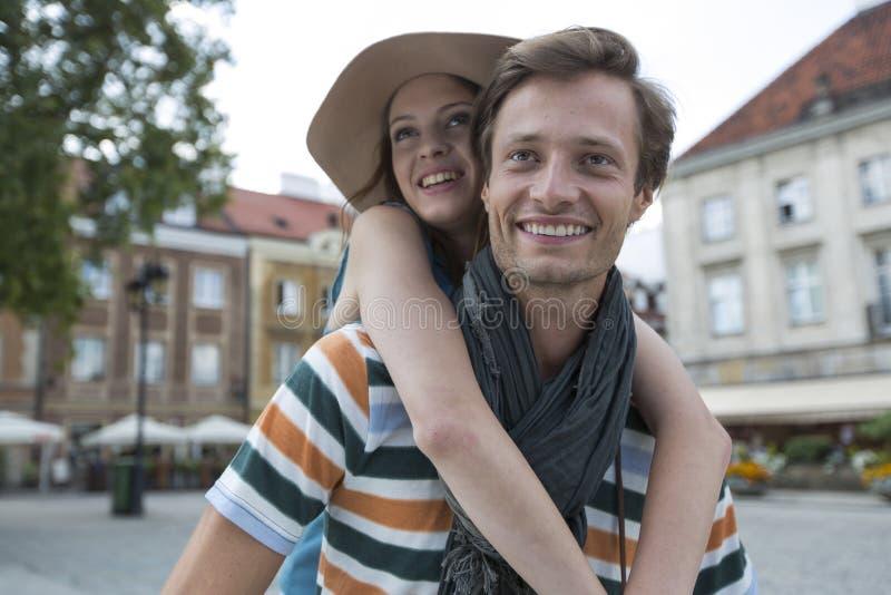 Uomo felice che trasporta sulle spalle donna sulla via durante la vacanza fotografie stock