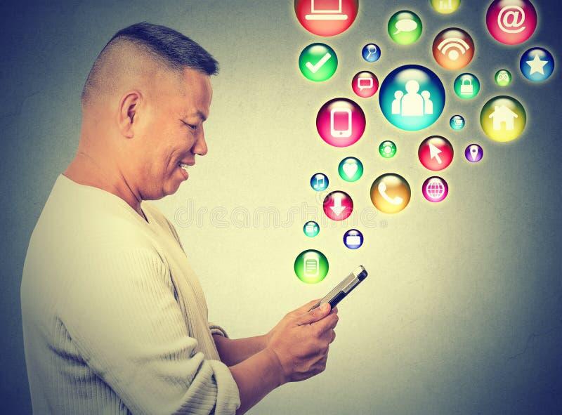Uomo felice che usando mandare un sms sulle icone dell'applicazione sociali di media dello smartphone che volano su immagini stock