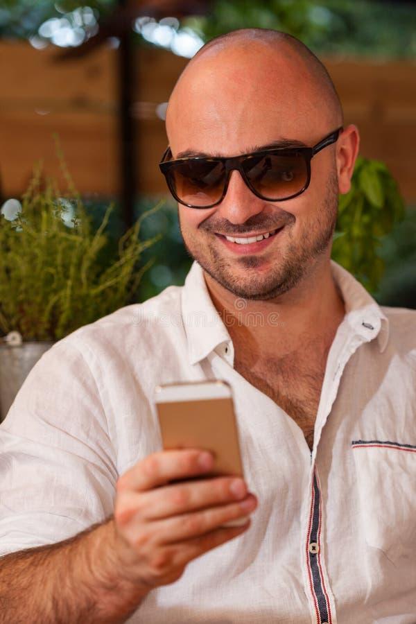 Uomo felice con gli occhiali da sole che esaminano il suo telefono immagine stock libera da diritti