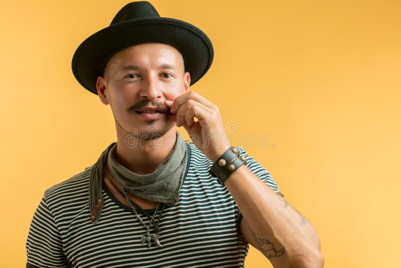 Uomo felice con il cappello d'uso dei baffi isolato sopra fondo giallo fotografie stock