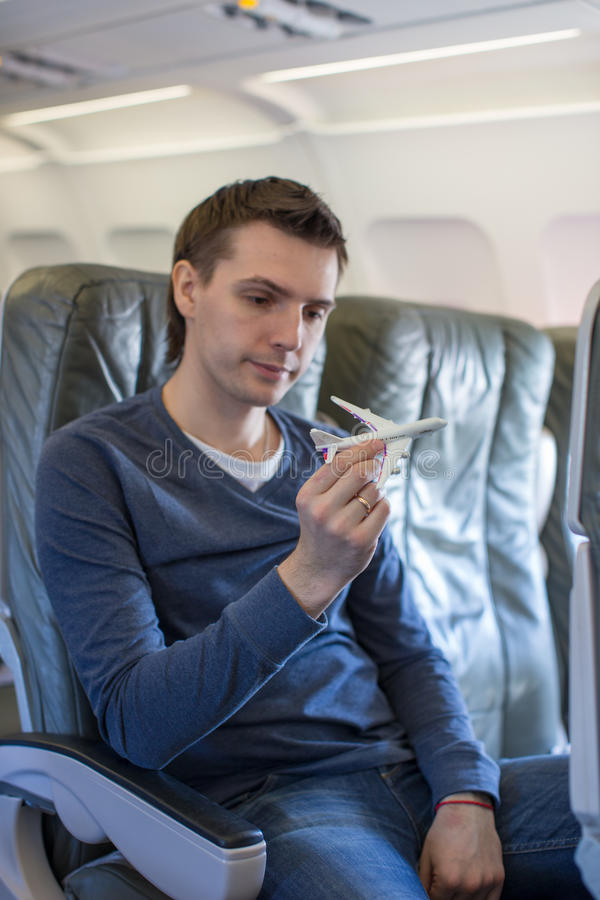 Uomo felice con il piccolo aeroplano di modello dentro un grande aereo immagine stock libera da diritti
