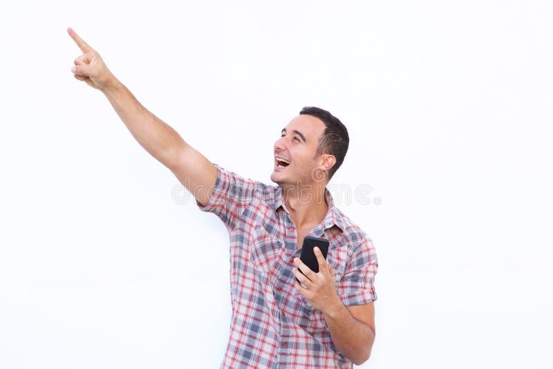 Uomo felice con il telefono cellulare ed indicare su sul fondo bianco isolato fotografia stock libera da diritti