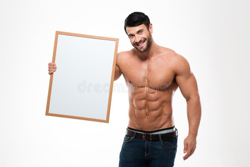 Uomo felice con il torso muscolare che tiene bordo in bianco fotografie stock