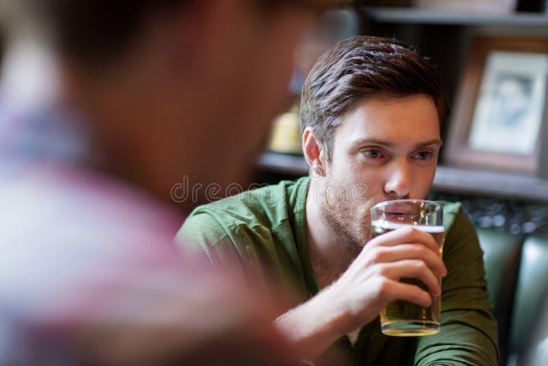 Uomo felice con la birra bevente dell'amico alla barra o al pub immagini stock libere da diritti