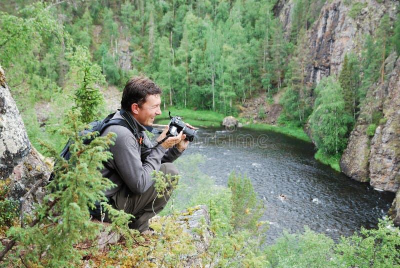 Uomo felice con la macchina fotografica sulla parte superiore della foresta di taiga. fotografia stock libera da diritti