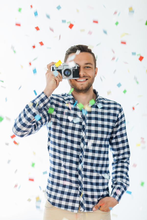 Uomo felice con la retro caduta dei coriandoli e della macchina da presa immagine stock libera da diritti