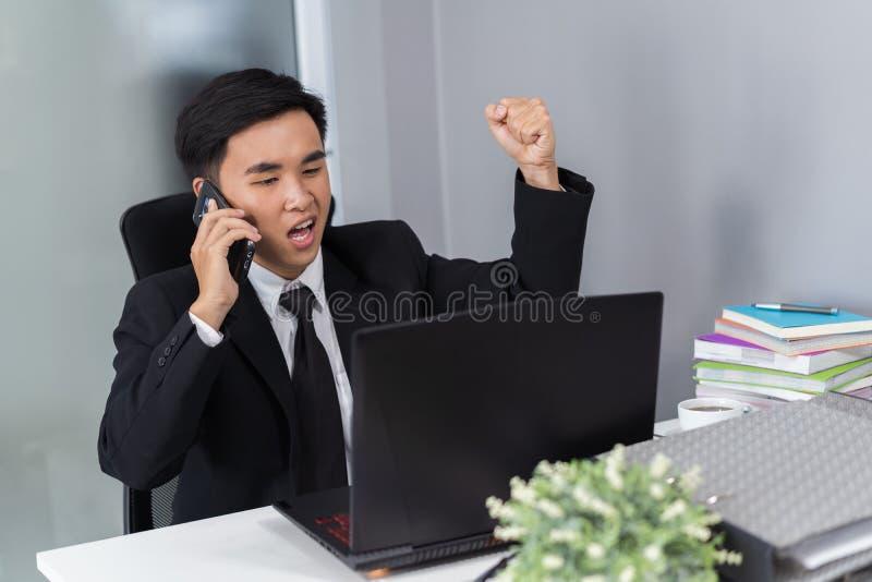 Uomo felice di affari che parla sul telefono cellulare e che per mezzo del computer portatile immagini stock