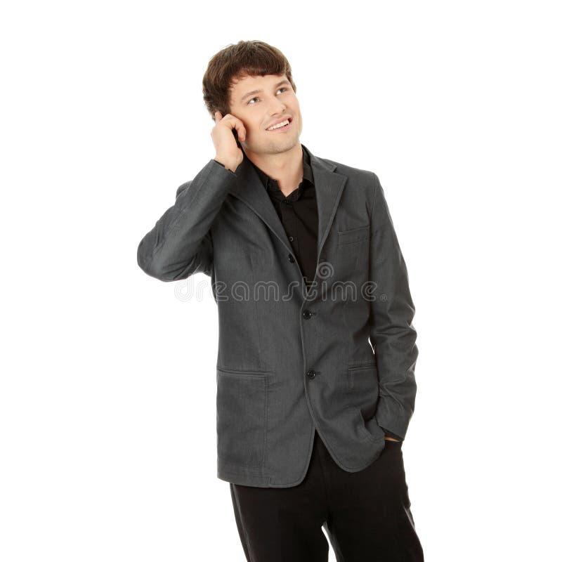 Uomo felice di affari che per mezzo del telefono mobile fotografia stock