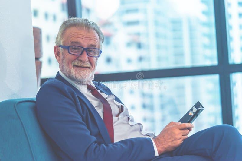 Uomo felice di affari che tiene un telefono cellulare per il concetto esecutivo di comunicazione fotografia stock