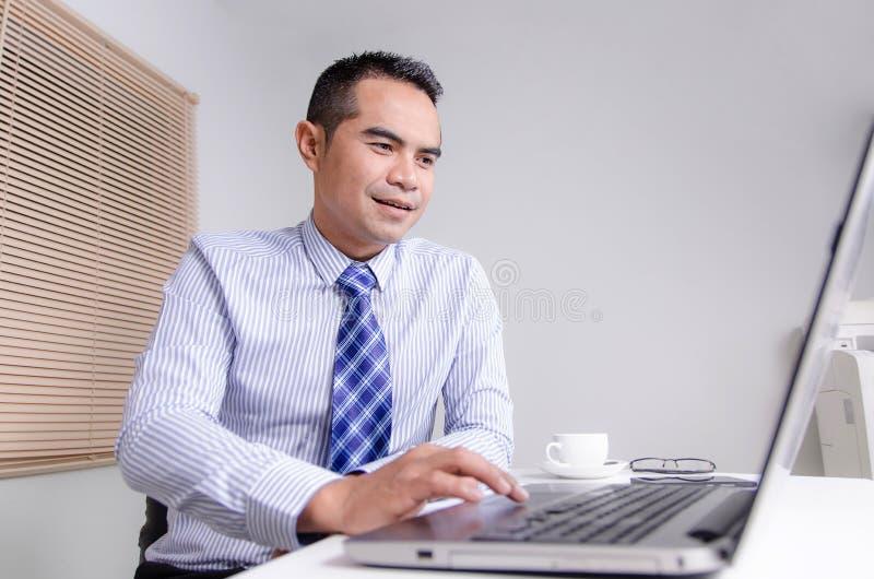 Uomo felice di affari di sorriso che utilizza computer portatile nell'ufficio fotografie stock libere da diritti