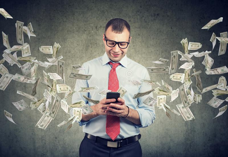 Uomo felice di affari facendo uso dello smartphone con le banconote in dollari che volano a partire dallo schermo fotografia stock