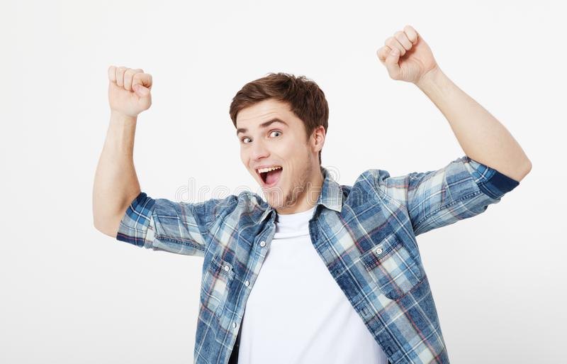 Uomo felice emozionante pazzo del ritratto che sta con le mani sollevate e che esamina macchina fotografica isolata su fondo bian immagine stock
