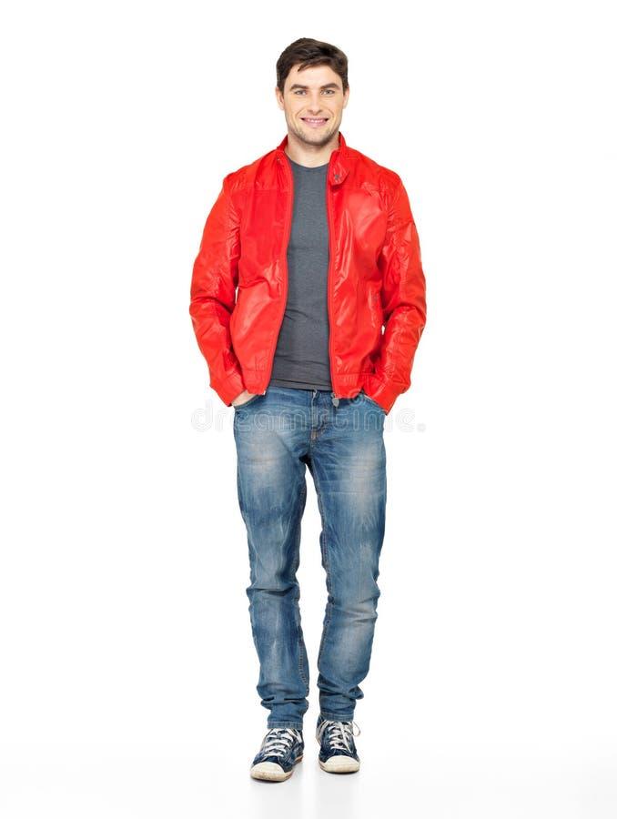 Uomo felice sorridente in rivestimento, in blue jeans e nei gymshoes rossi. immagine stock