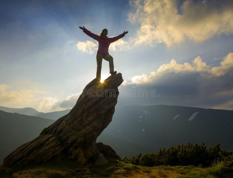 Uomo felice sulla roccia più precisamente - una donna fotografia stock