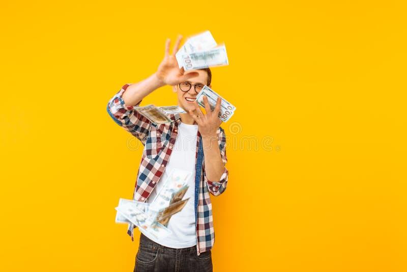 Uomo felice, vetri d'uso e una camicia di plaid, gettante fuori le banconote dei soldi su un fondo giallo fotografia stock libera da diritti