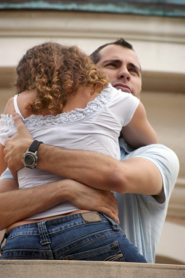 Uomo fiero bello che abbraccia fine della donna sul balcone fotografia stock libera da diritti